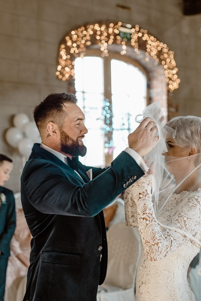 groom lifts veil off brides face