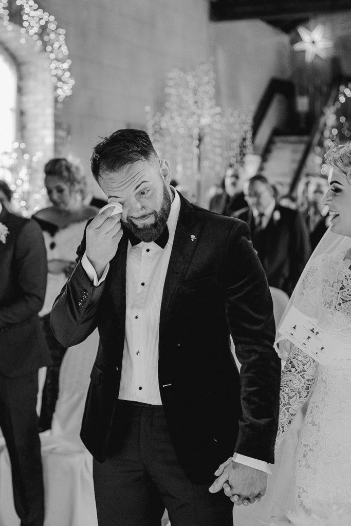 groom wipes away tears