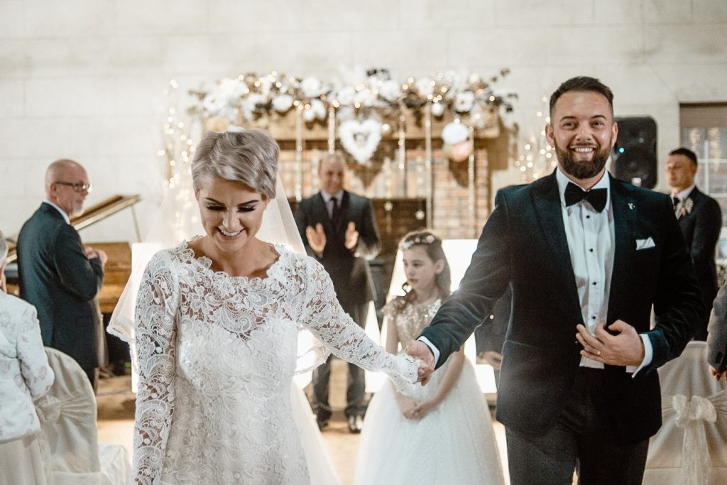 bride and groom walking down aisle celebrating