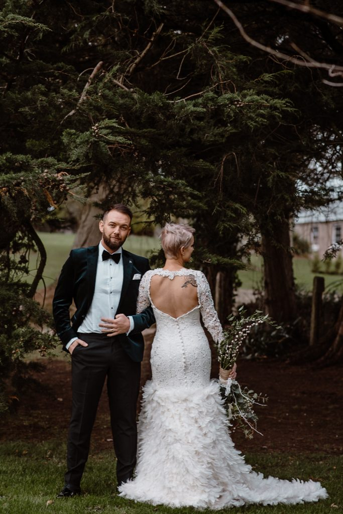 groom faces camera and bride shows back of dress