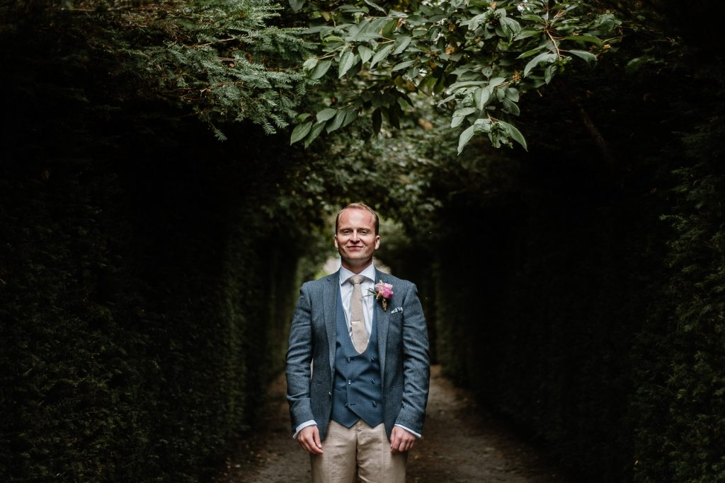 portrait of groom standing in nice light among trees
