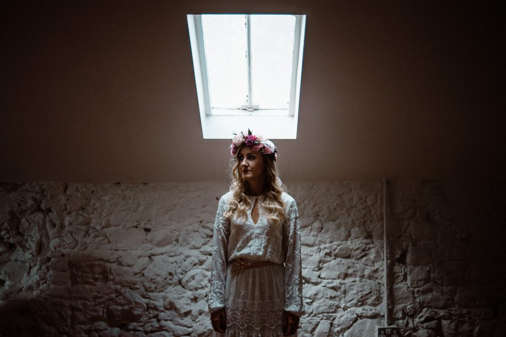 bride standing under window light coming down from above with flower crown