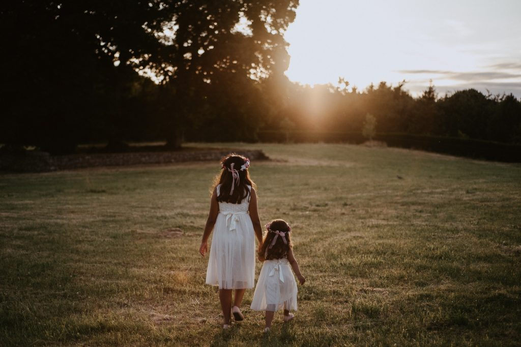 two little flower girls walk hand in hand in a field at sunset