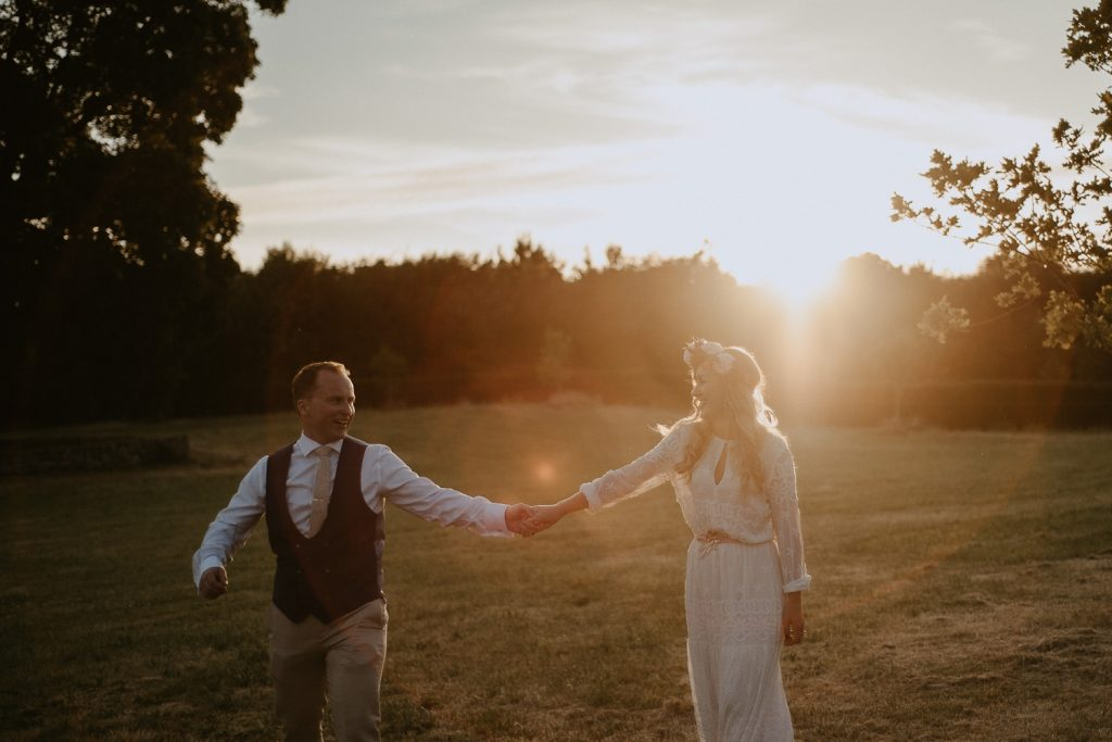 couple walking hand in hand smiling at sunset