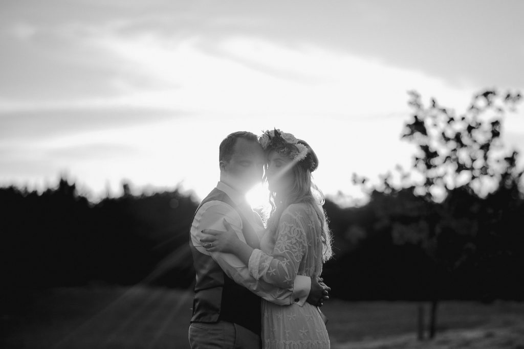 bride and groom facing each other as the sun rays come between their faces