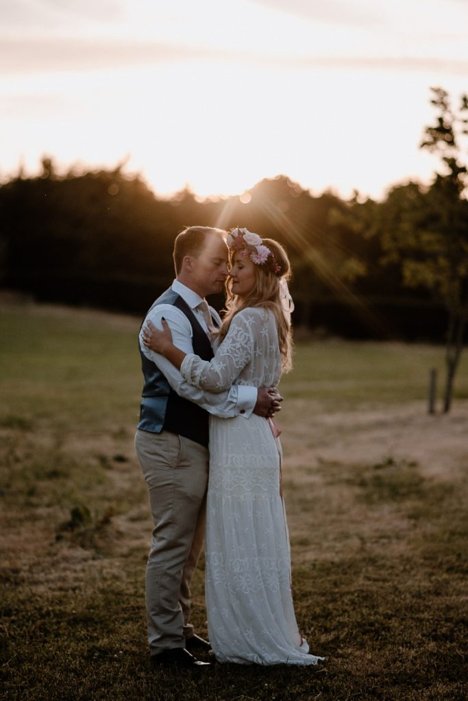 full length portrait of bride and groom in field at sunset