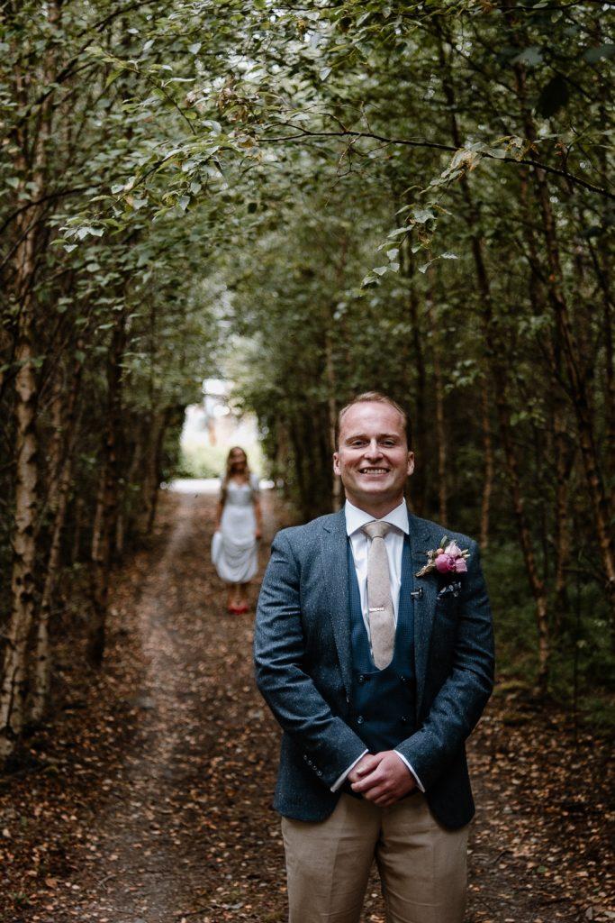 excited happy groom as bride is walking behind him