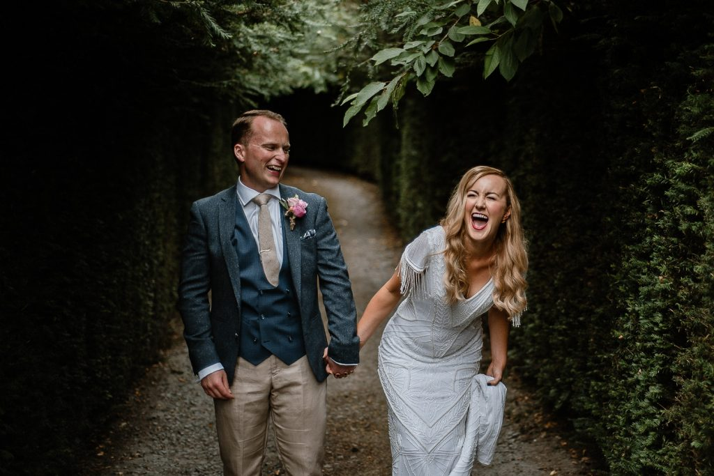 bride doubled over laughing at her groom