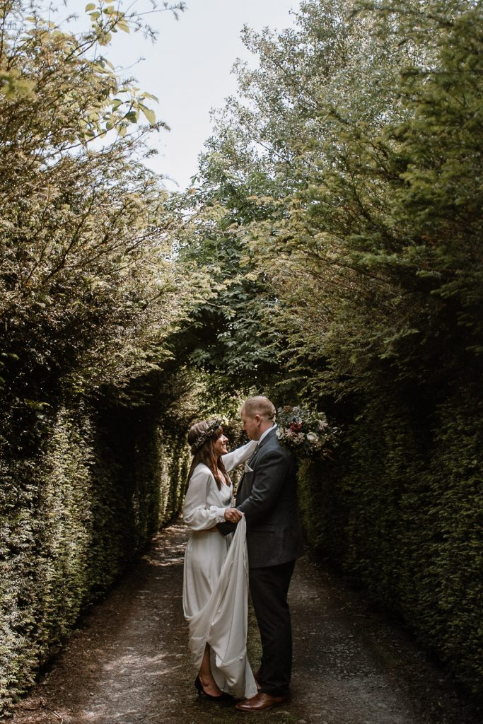 bride and groom facing each other under trees