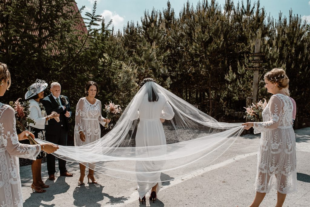 bridesmaids stretching out brides veil