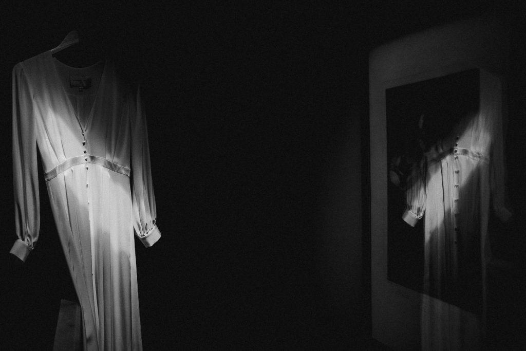 wedding dress in harsh light reflected in glass.