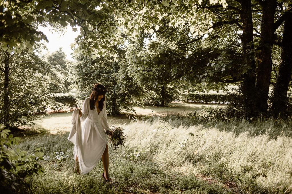 bride walking into forest holing dress up