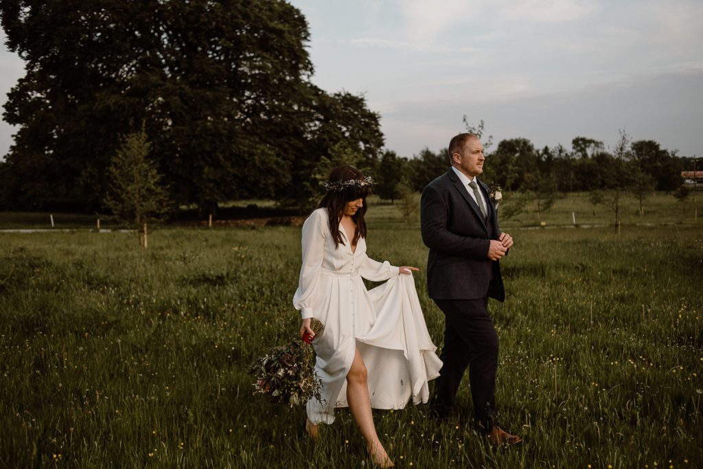 brid and groom walking into field at sunset