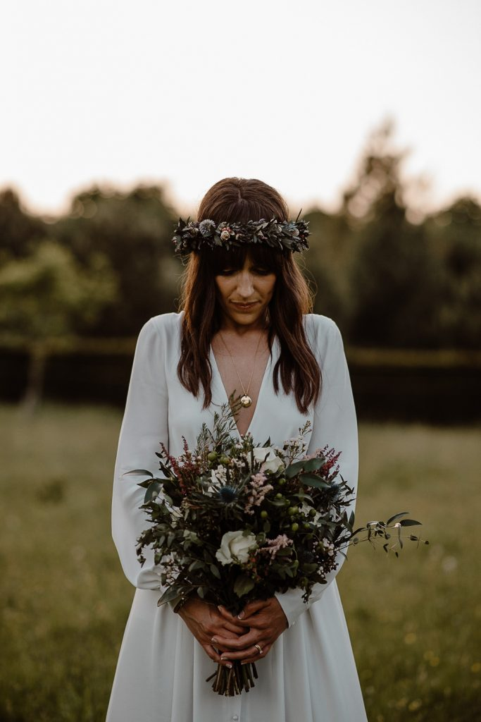 boho bride standing in a field holding her flowers