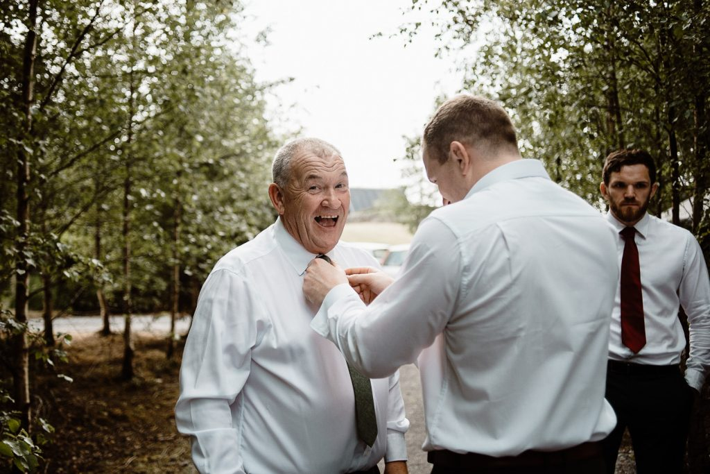 Happy face of grooms father getting tie done