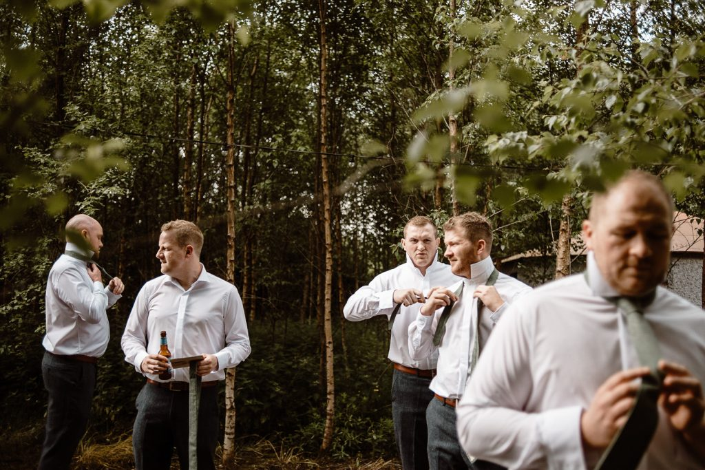 groomsmen getting ready outside in nature