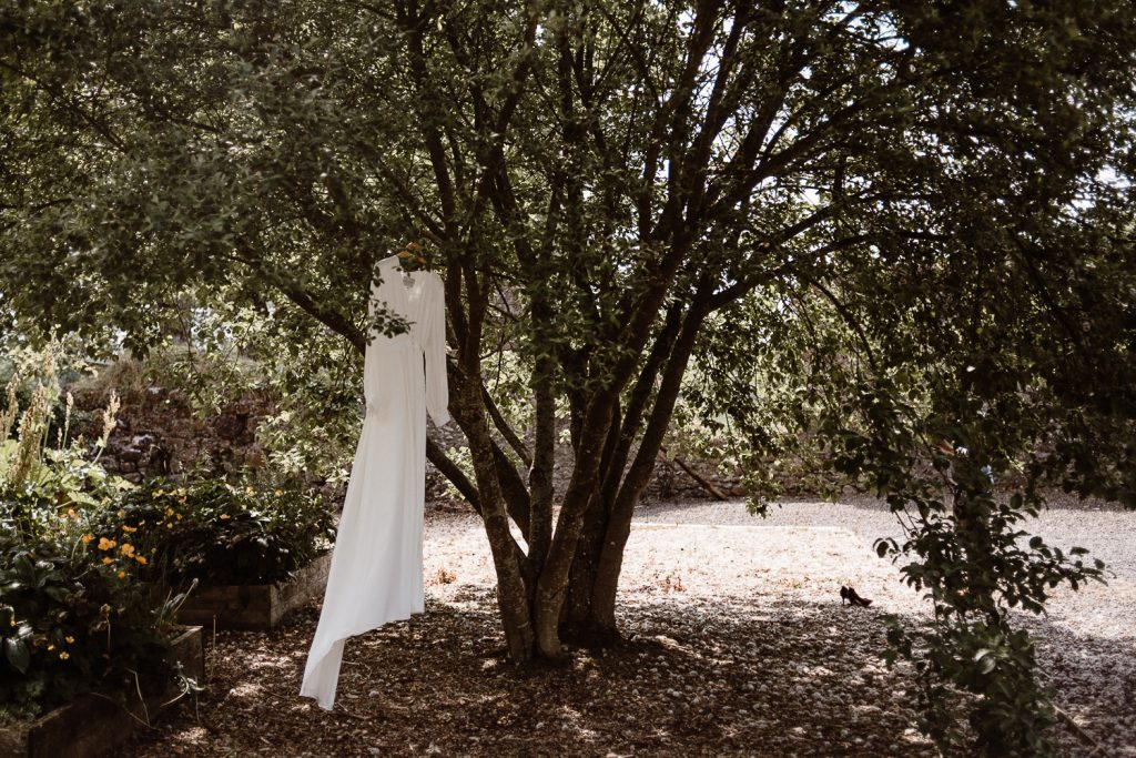 wedding dress hanging on tree
