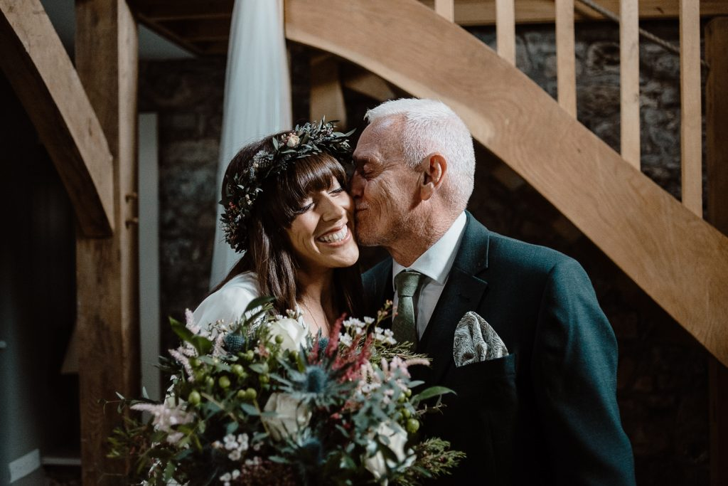 father kisses bride on cheek