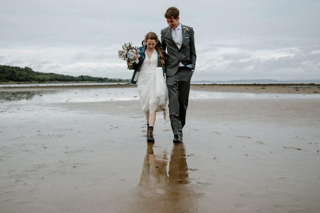 bride and groom walk towards camera