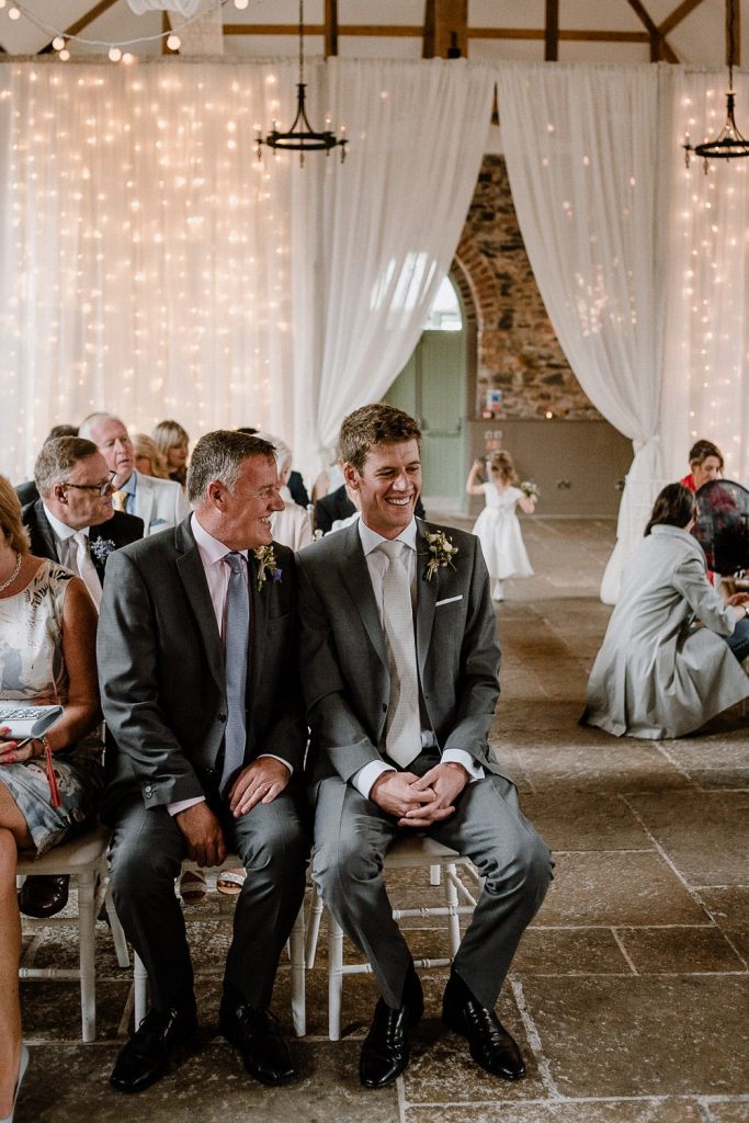 groom waits at the top of the aisle