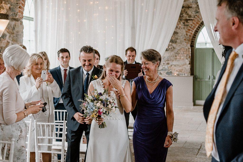 bride cries as she walks up the aisle