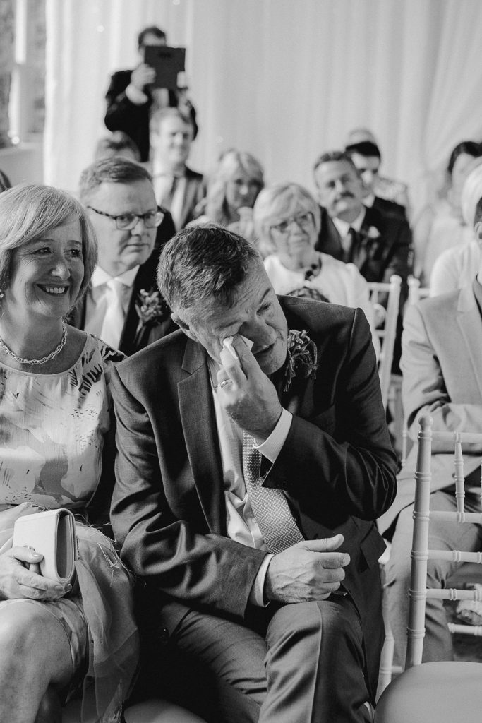 grooms father wipes tears away