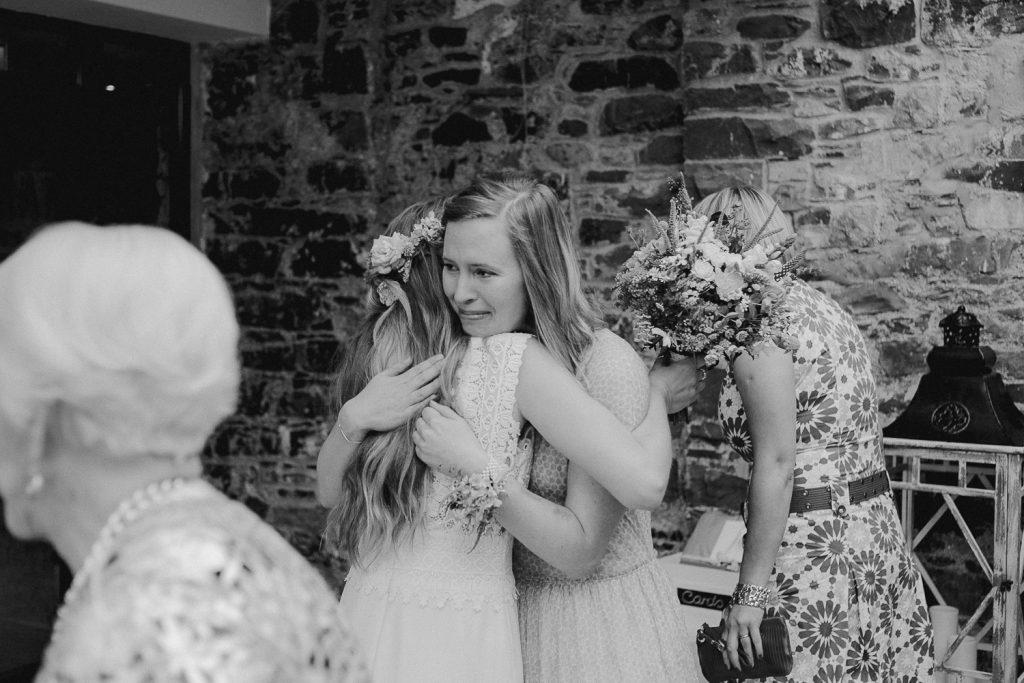 bridesmaid hugs the bride crying