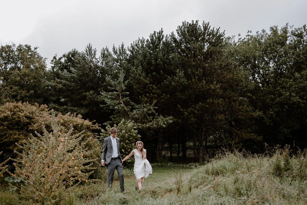 bride and groom walk out in long grass