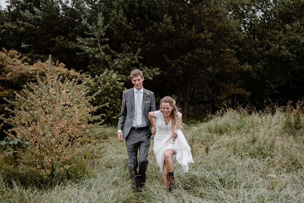bride pulls groom into the grass