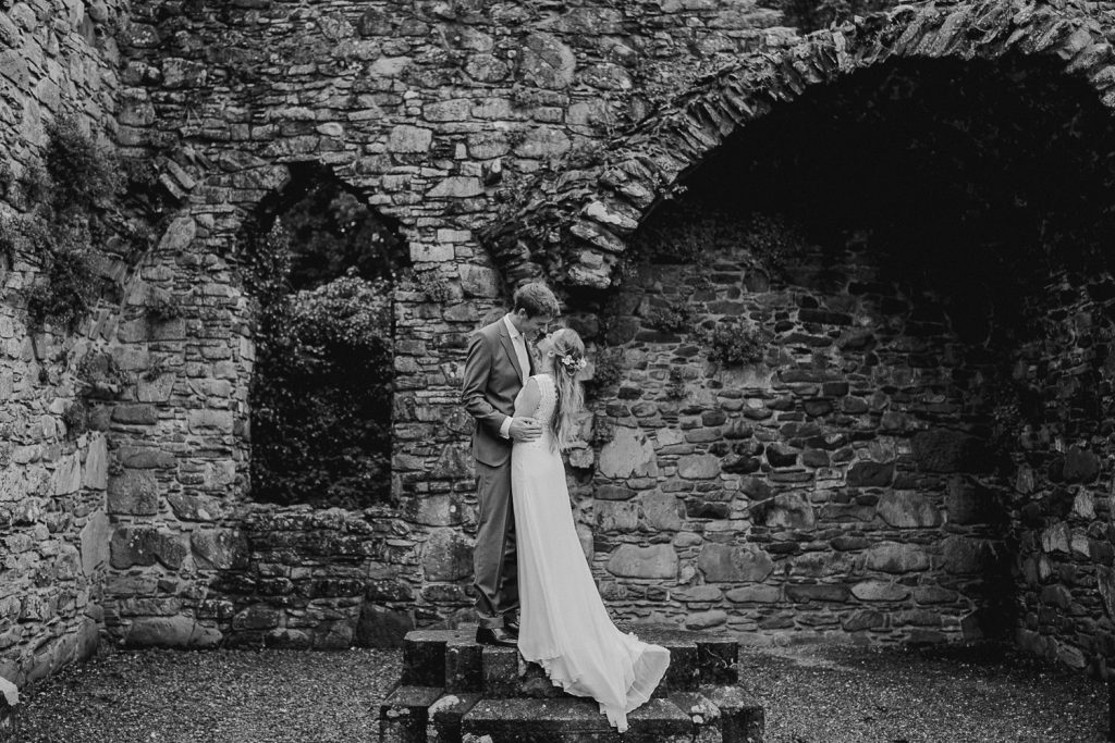bride stands on wall and dress hangs down