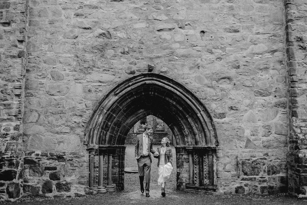 bride and groom walk out under arch