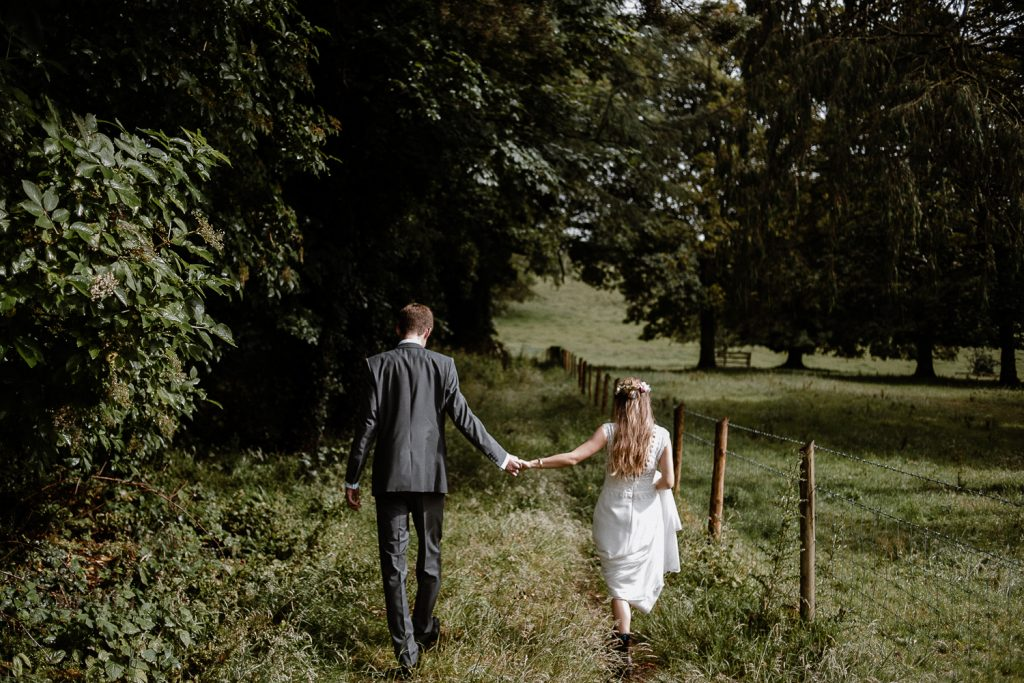 bride and groom walk hand in hand in field