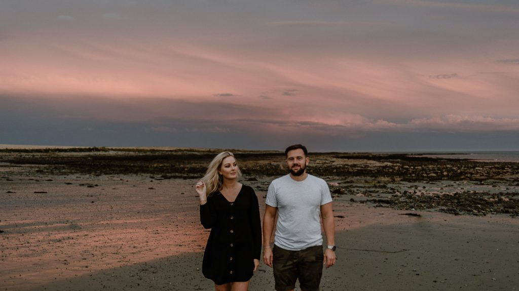 couple, male and flam standing on beach with a beautiful pink sky