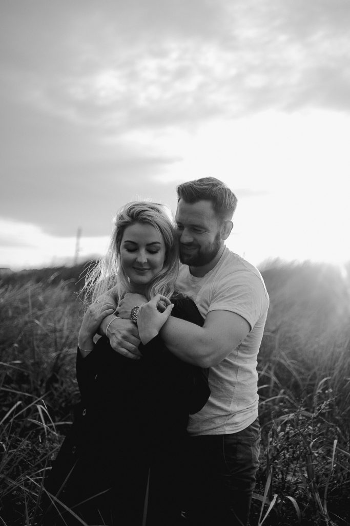 couple hugging in long grass at sunset