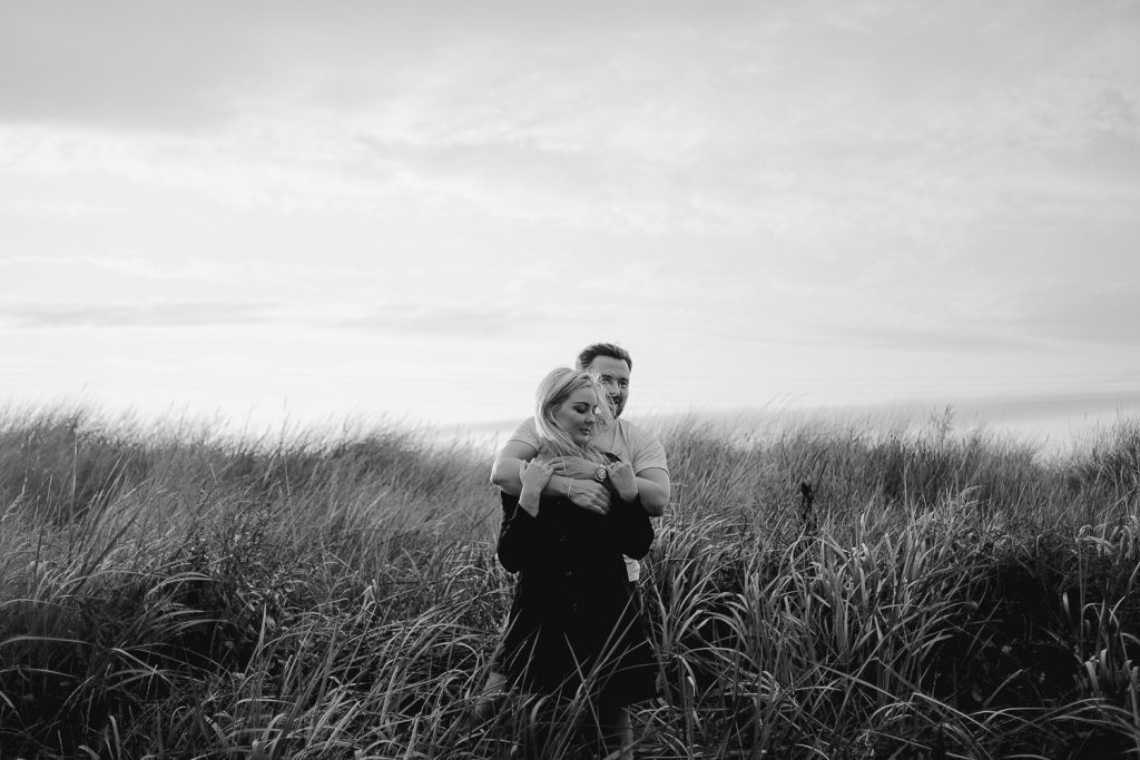 couple hugging in long grass