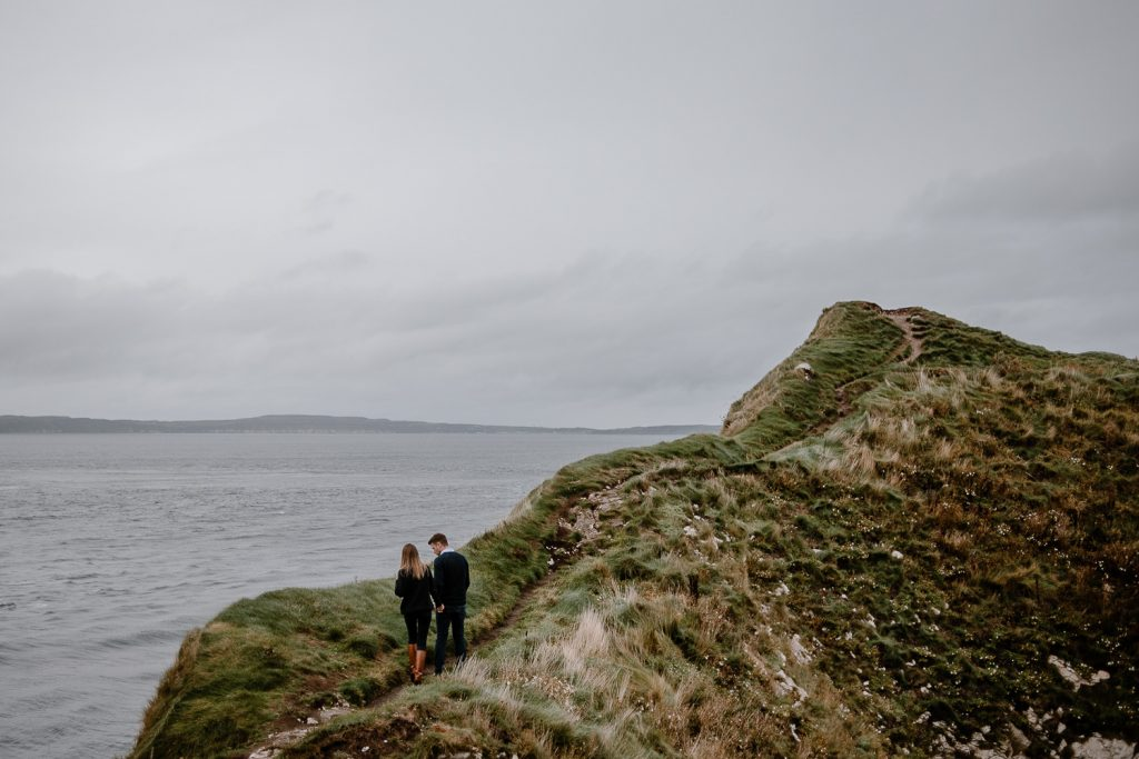 irish landscape of cliff and couple walking