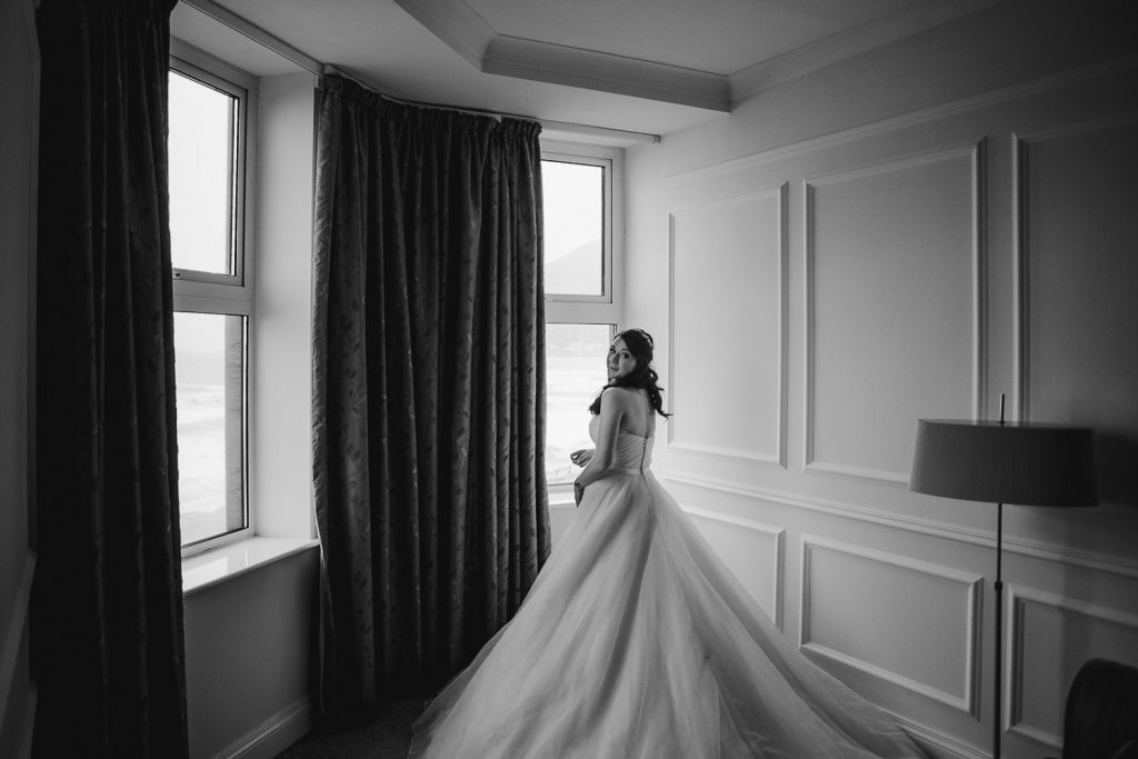 bride standing at window in very big dress.
