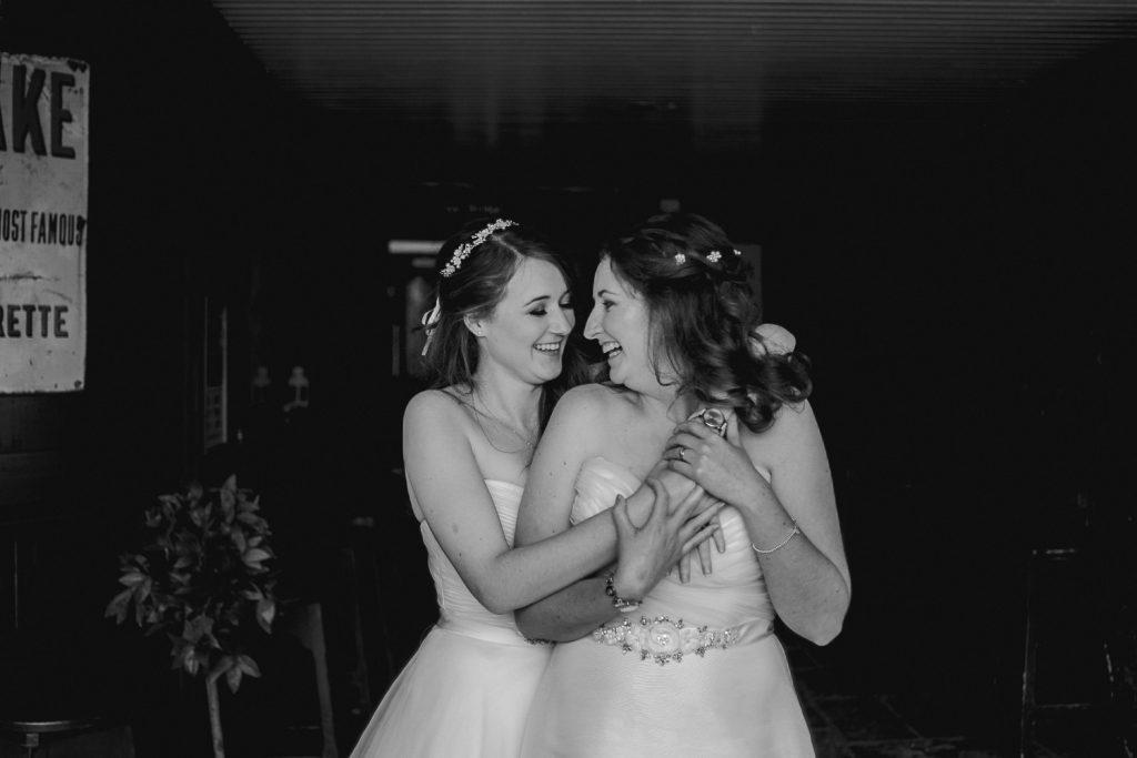 two brides hugging together. same sex wedding