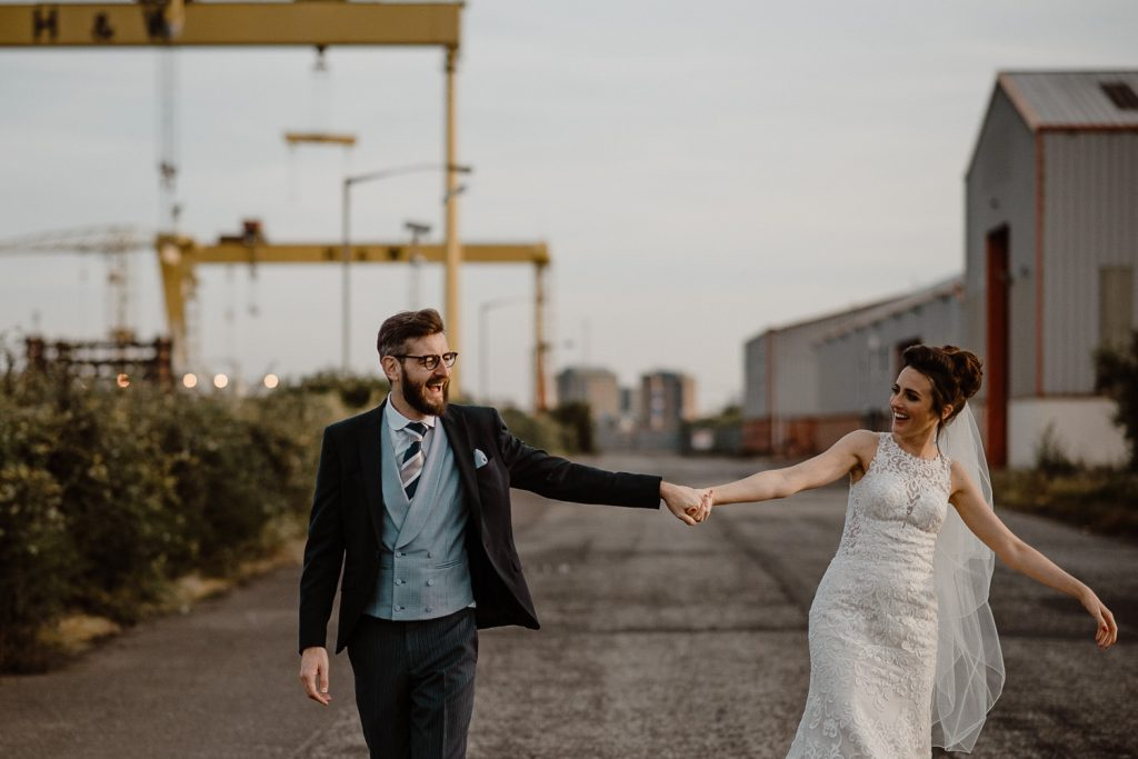 bride and groom walking hand and hand at harland and wolf belfast