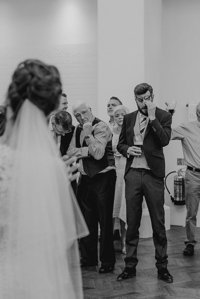 groom wipes away tears as he watches father daughter dance