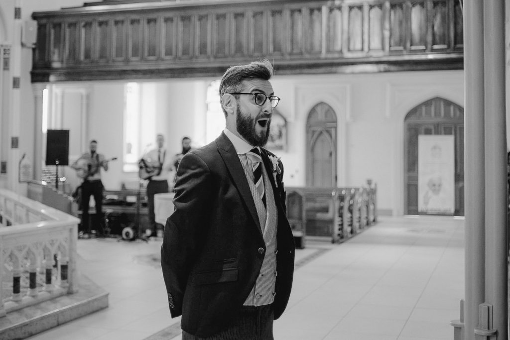 extremely happy groom when he sees beautiful bride waking down aisle