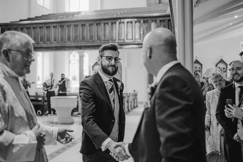proud groom shaking hand of father of the bride