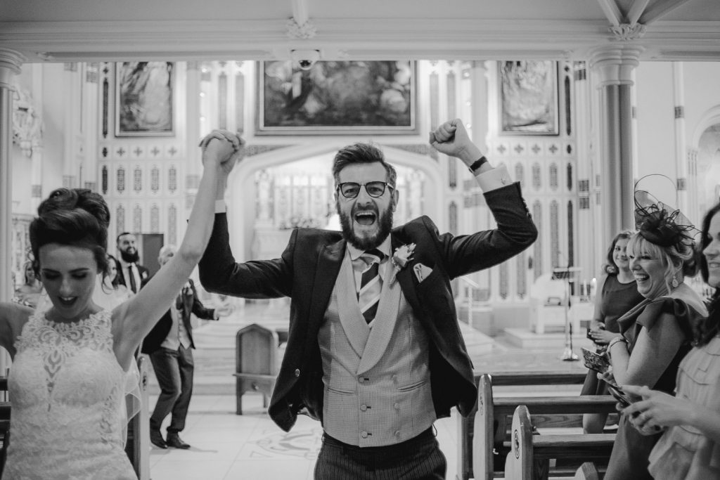 groom cheering in celebration at wedding
