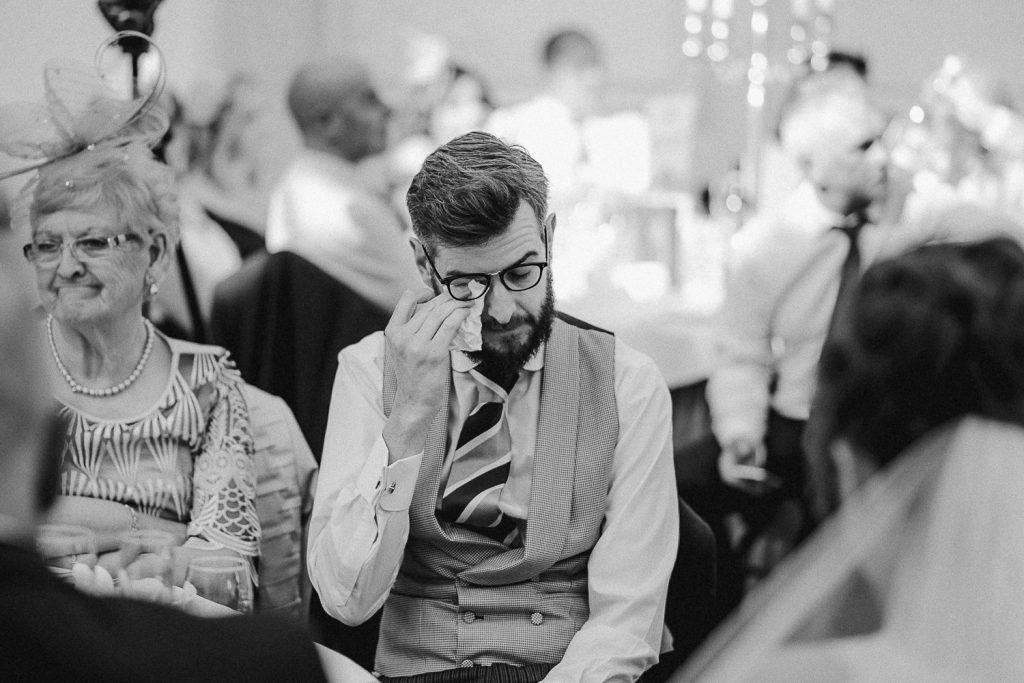 groom wipes away tears during speech