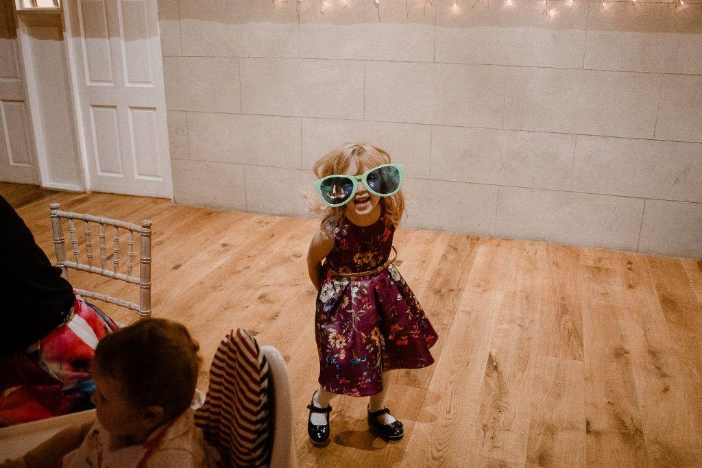 little girl wearing dress and big joke glasses