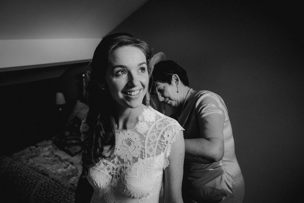 brides mum buttoning her dress