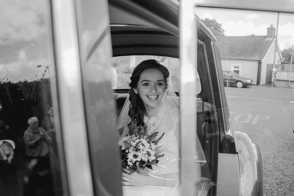 bride in wedding car at church