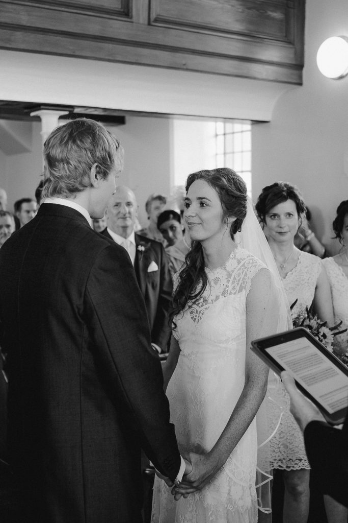 bride standing looking at groom vows