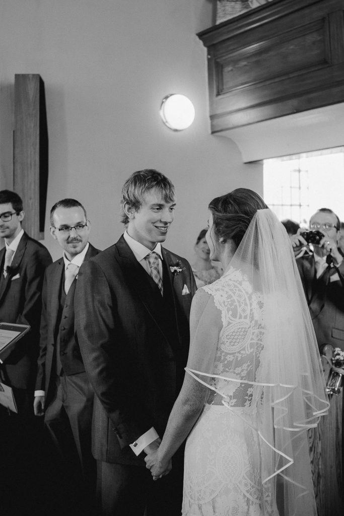 groom standing looking at bride