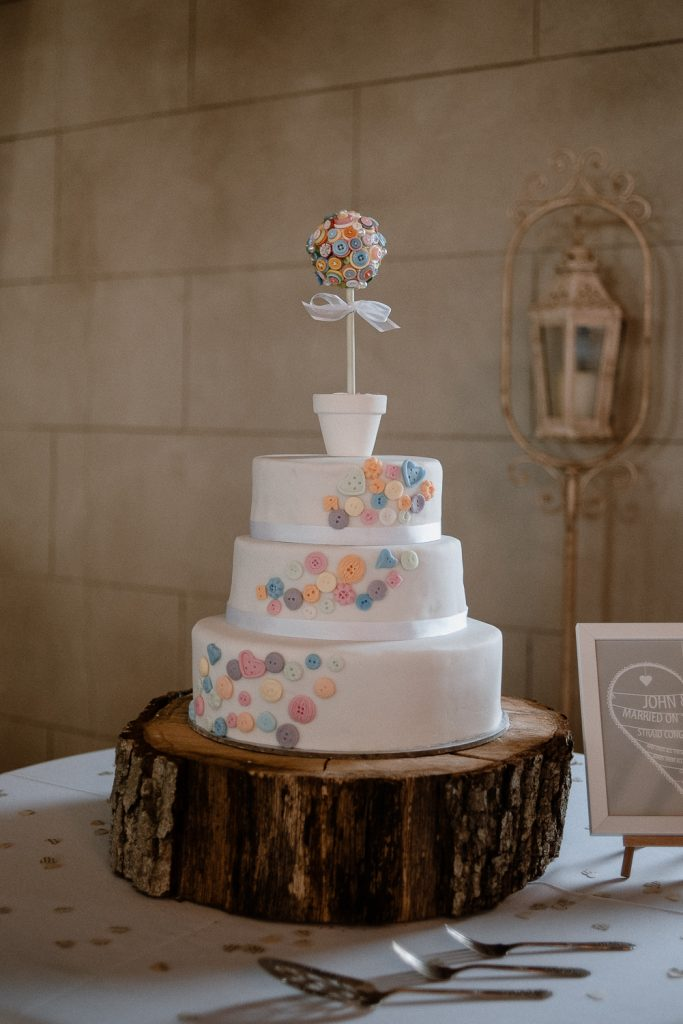 white wedding cake with button pattern